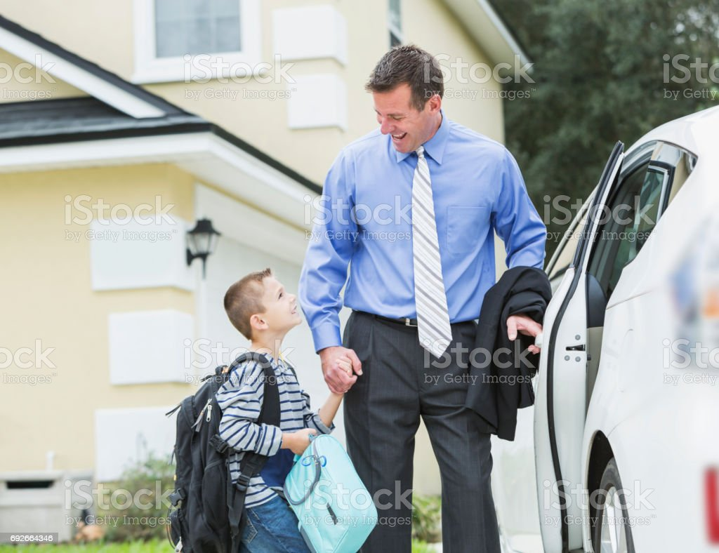 Businessman taking boy to school, walking to car stock photo