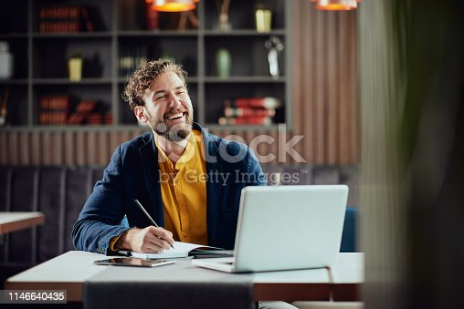 944992706 istock photo Businessman taking notes and looking at laptop while sitting in cafe. 1146640435