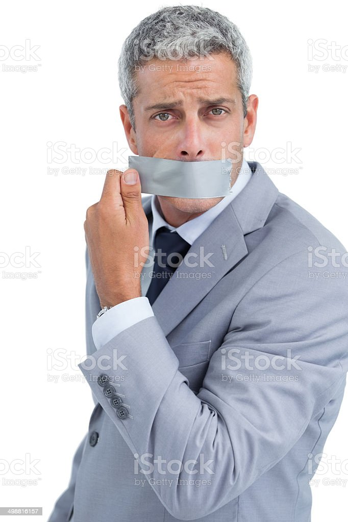 Businessman taking off duct tape on mouth stock photo