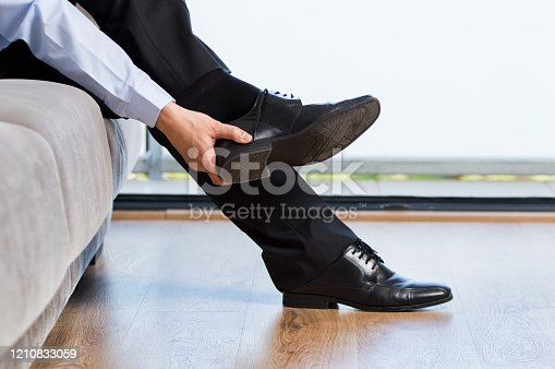 Profile of a tired businessman taking off shoes after work at home