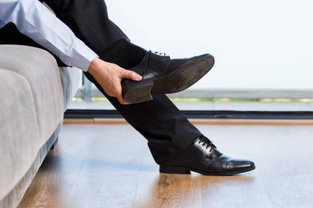 businessman taking off shoes after work at home stock photo