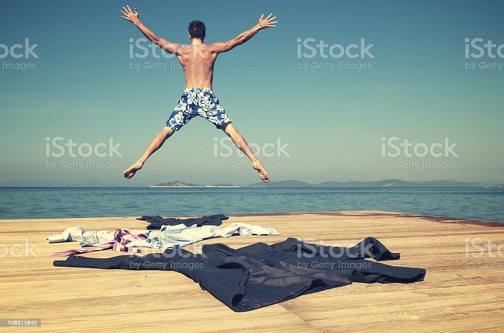 Businessman Taking Off Suit and Jumping into the Sea royalty-free stock photo