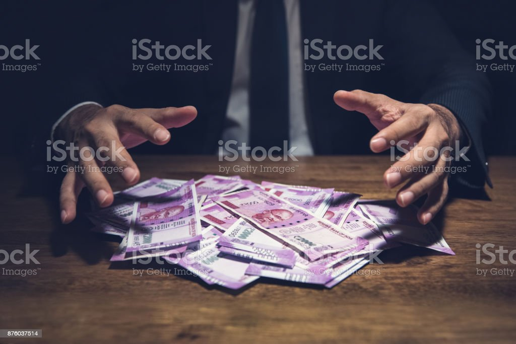Businessman taking pile of money, Indian Rupee banknotes, on his desk in a dark office. stock photo