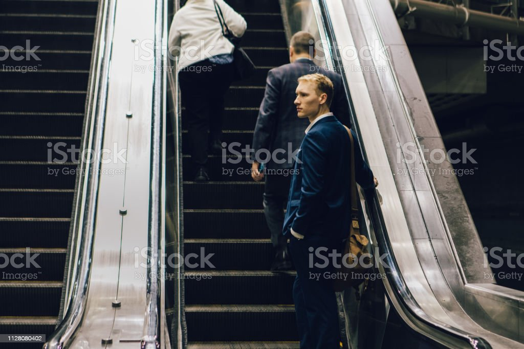 businessman taking the escalator stock photo
