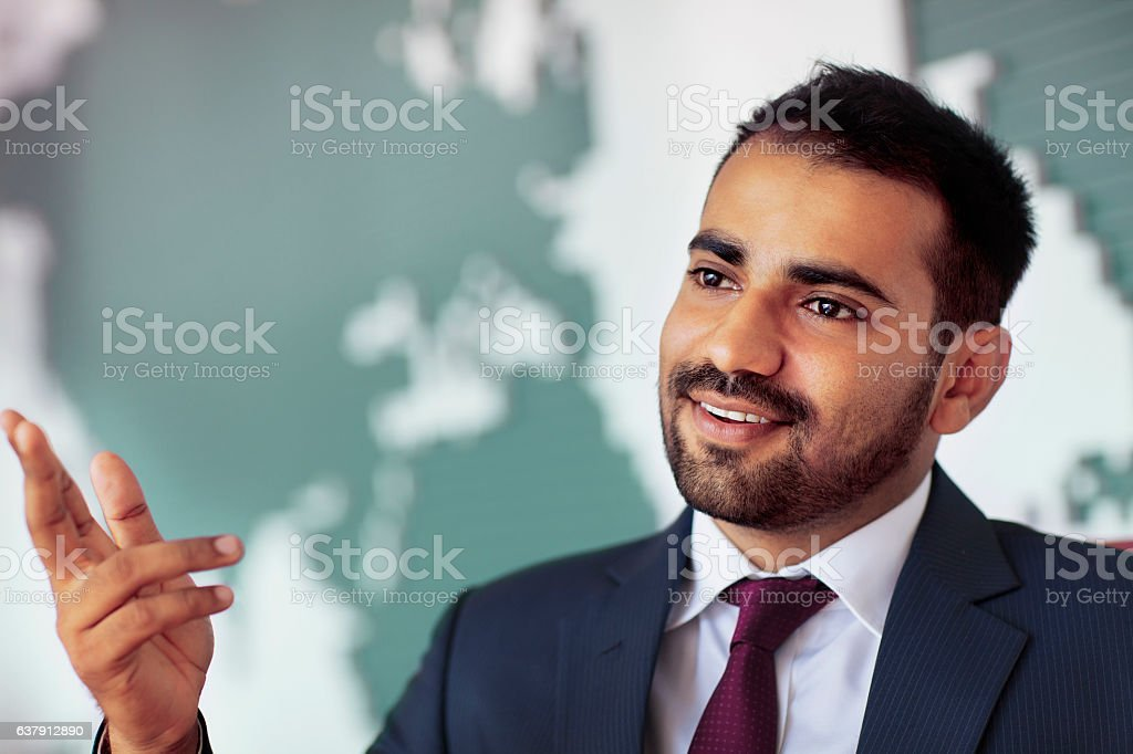 Businessman talking in room with map on wall stock photo