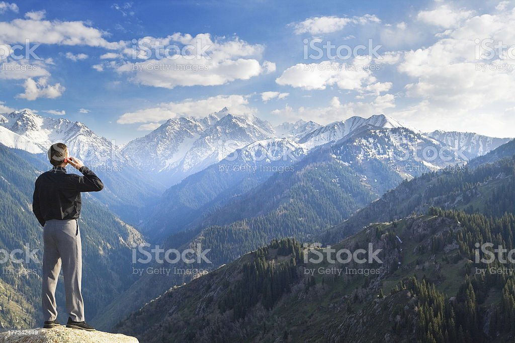 Businessman talking on a cellphone on a mountain stock photo
