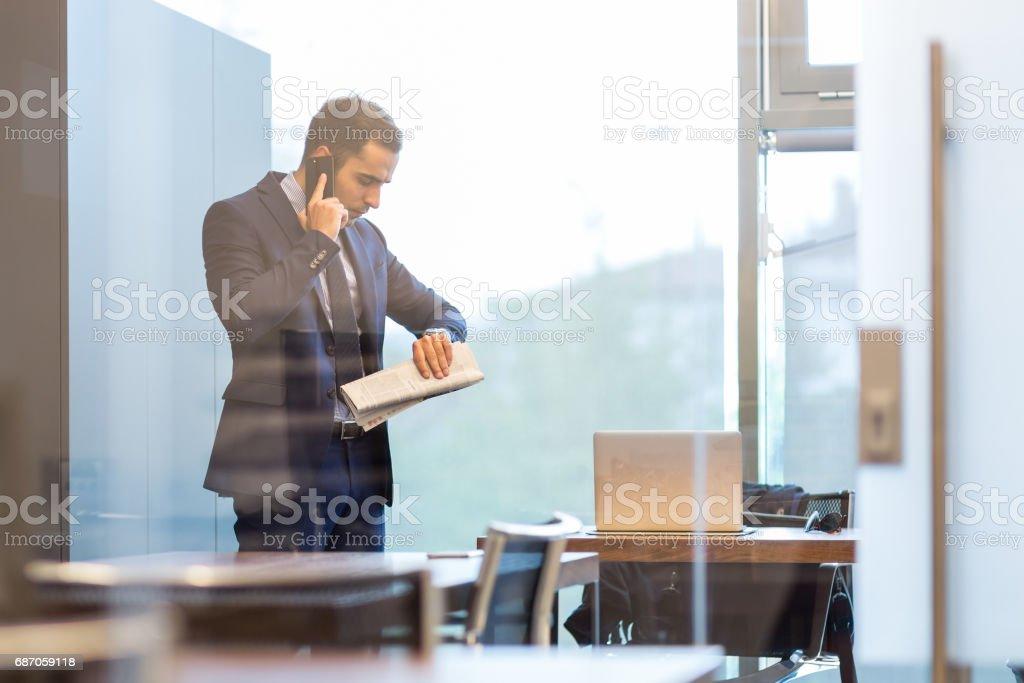 Geschäftsmann sprechen auf einem Handy beim Betrachten der Armbanduhr. – Foto