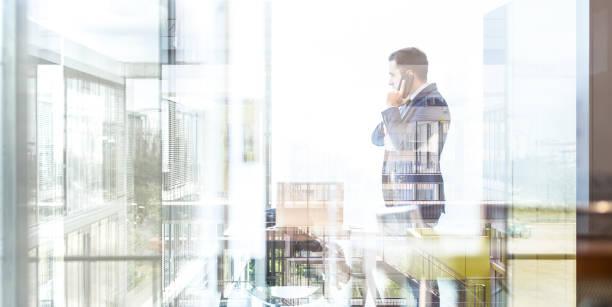 Homme d'affaires, parler sur un téléphone mobile tout en regardant par la fenêtre. - Photo