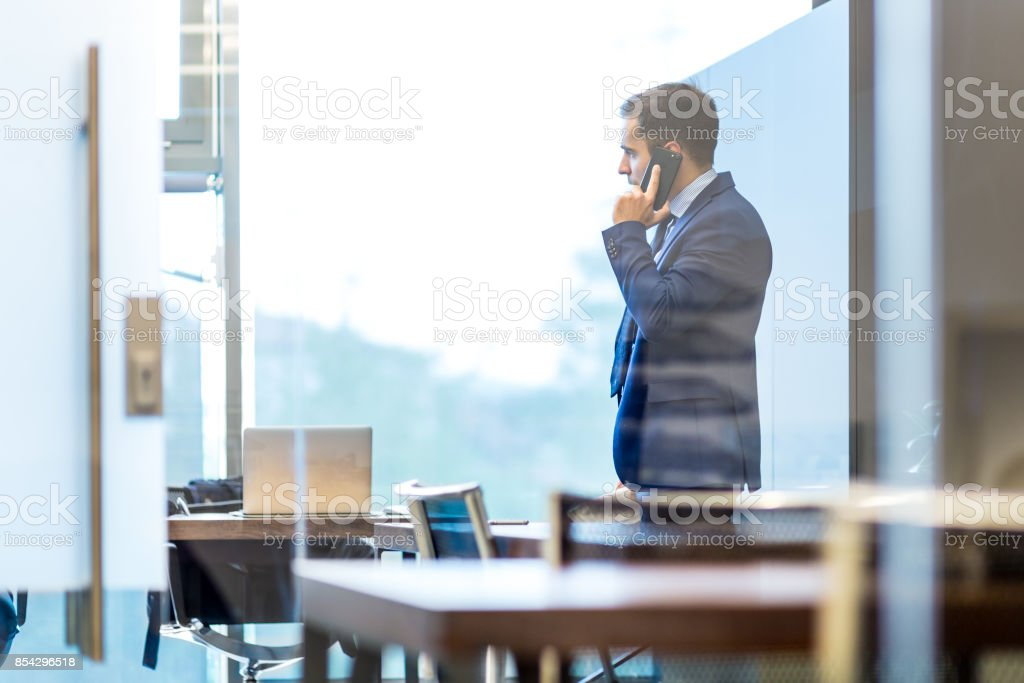 Geschäftsmann sprechen auf einem Handy beim Blick durch Fenster. Lizenzfreies stock-foto