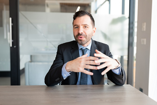 Businessman in suit talking to camera during a web conference in office