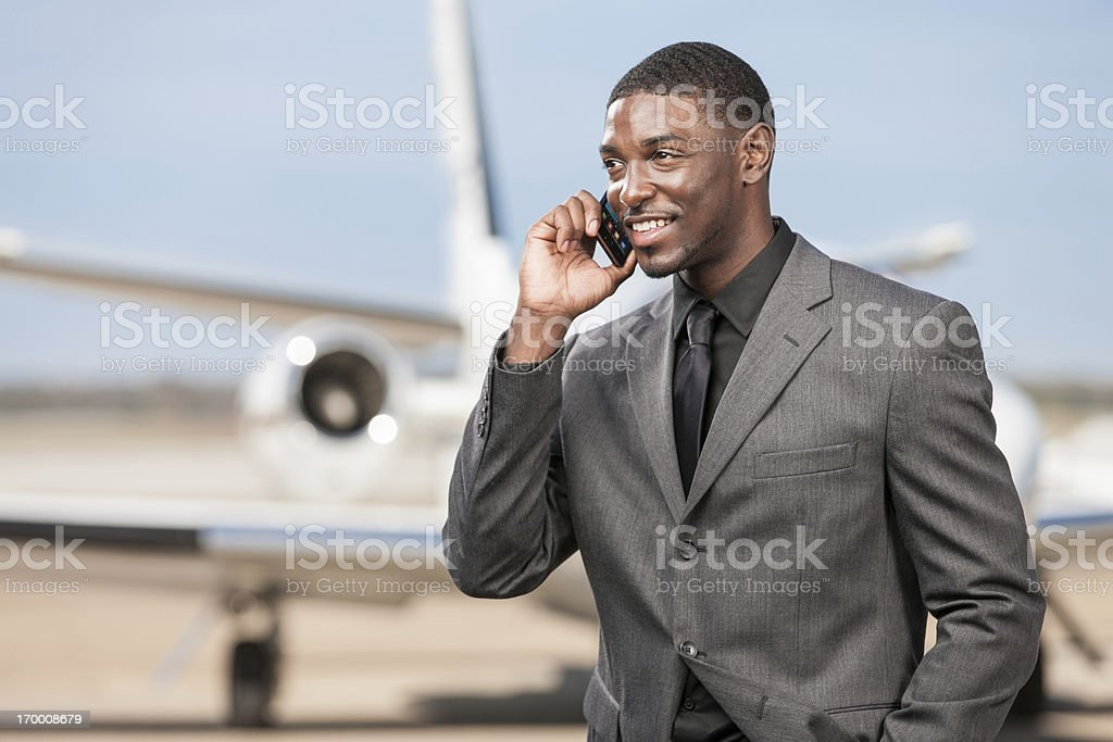 Businessman Talking on Cell Phone at Airport stock photo