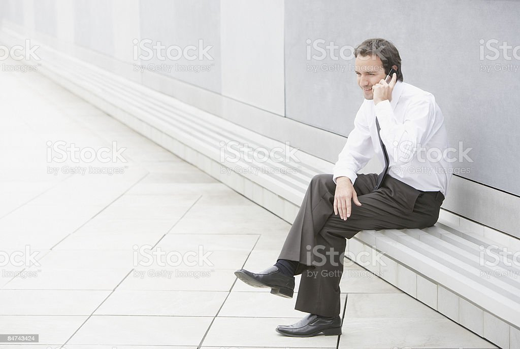 Businessman talking on cell phone in courtyard royalty-free stock photo