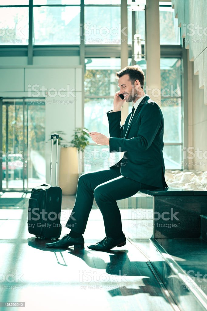 Businessman talking on cell phone in hotal hall Full lenght portrait of smiling businessman on business travel, wearing dark suit, sitting in a hotel hall and talking on mobile phone. Suitcase next to him. 2015 Stock Photo