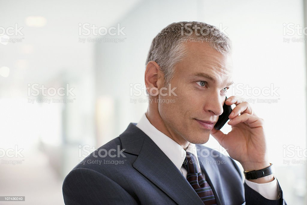 Businessman talking on cell phone in office royalty-free stock photo