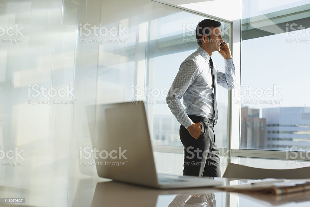 Businessman talking on cell phone in office stock photo