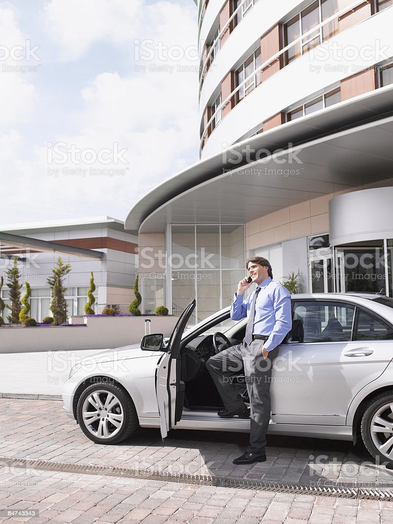 Businessman talking on cell phone next to car royalty-free stock photo