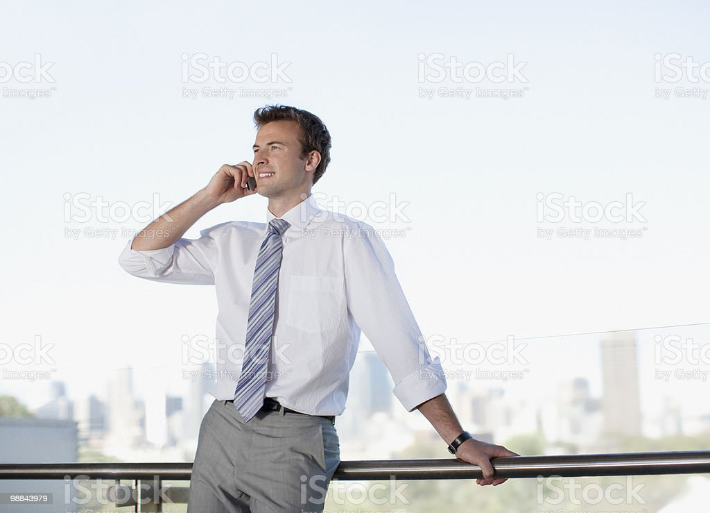 Businessman talking on cell phone on balcony royalty-free stock photo