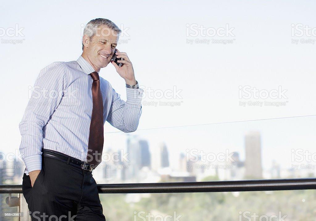 Uomo d'affari parlando sul cellulare sul balcone foto stock royalty-free