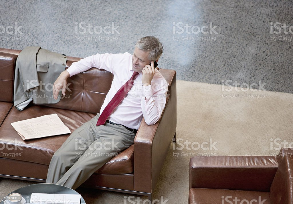 Businessman talking on cell phone on lobby sofa royalty-free stock photo