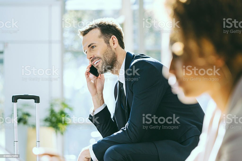 Businessman talking on cell phone Focus on the businessman sitting in a hotel hall and talking on mobile phone, suitcase next to him. 2015 Stock Photo
