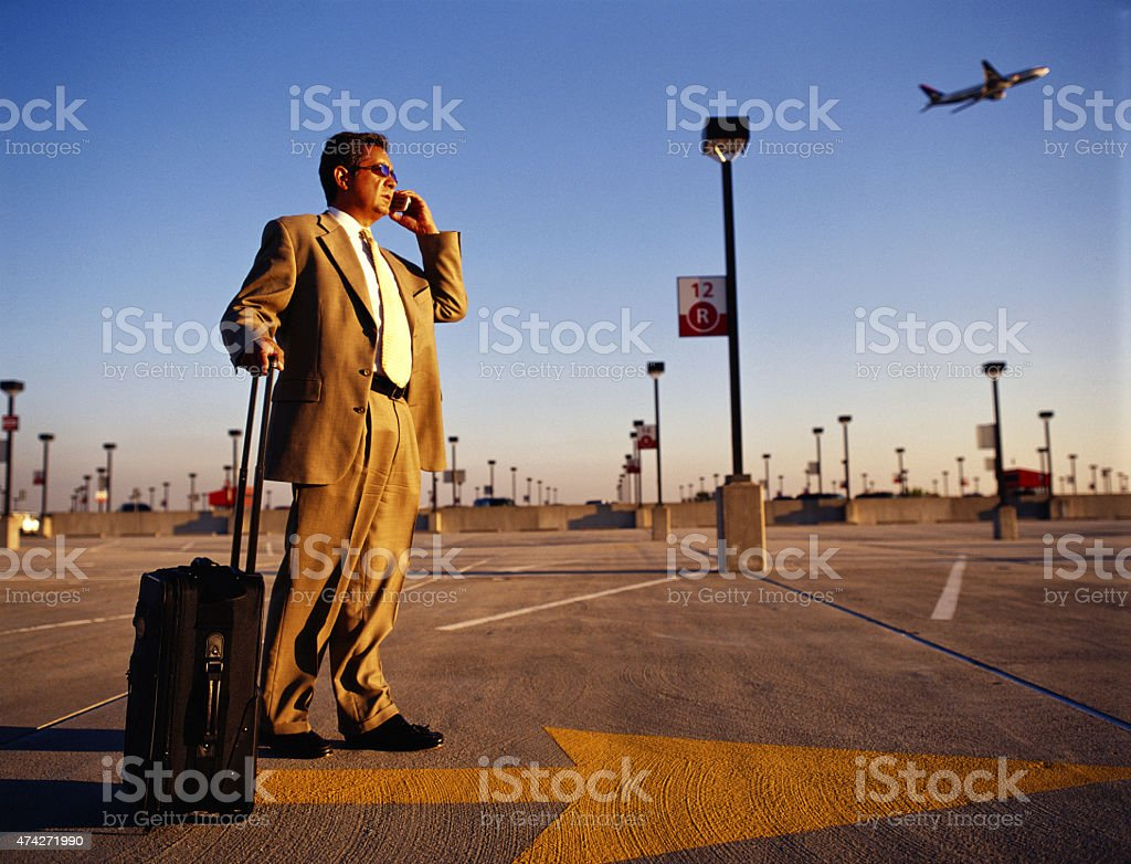 Businessman talking on cell phone waiting at airport. stock photo
