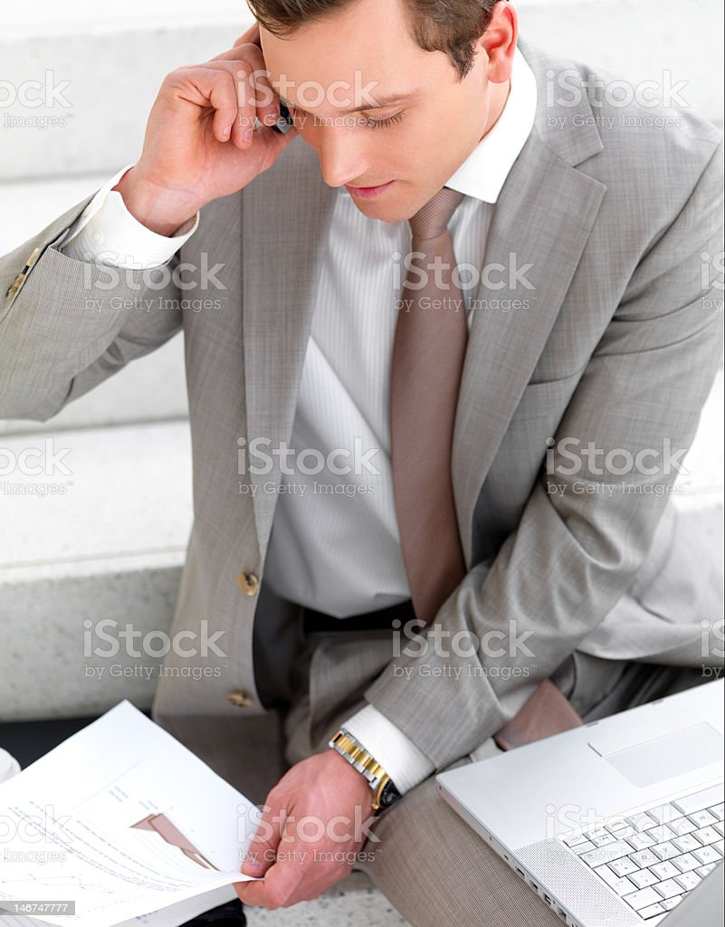 Businessman talking on cellphone with laptop and documents beside him royalty-free stock photo