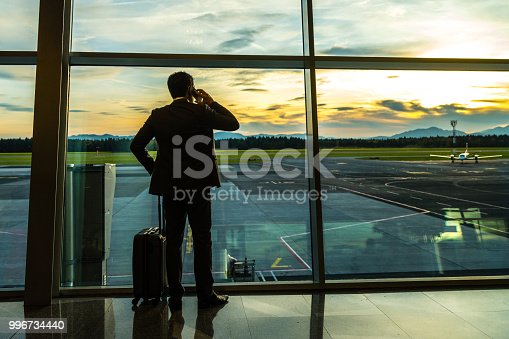 Businessman talking on mobile phone at airport departure area.