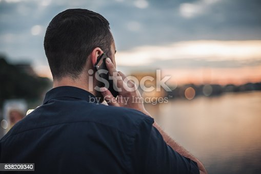 Businessman talking on mobile phone at sunset looking at evening city