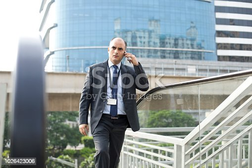 Indian businessman talking on mobile phone in city