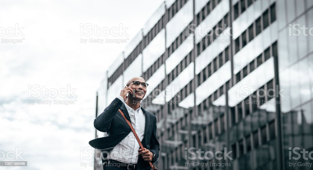 Smiling businessman talking over cell phone while commuting to office...