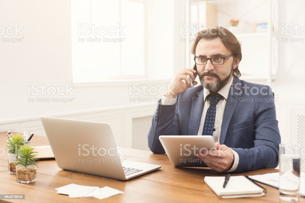 Businessman talking on phone and using tablet royalty-free stock photo