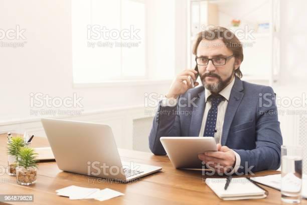 商人在電話和使用平板電腦交談 照片檔及更多 中老年人 照片