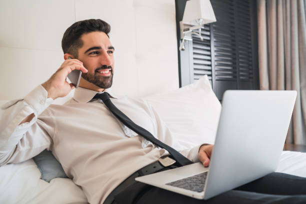 Businessman talking on phone at hotel room. stock photo