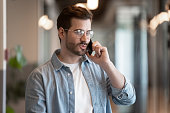 Handsome businessman wearing glasses talking on mobile phone solve business issues contact with company client distantly standing inside of modern office hall, working process during workday concept