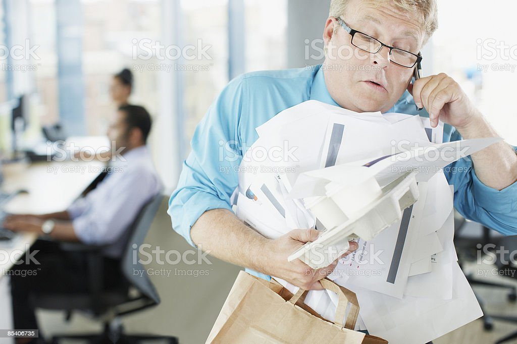 Businessman talking on phone holding paperwork and coffee stock photo