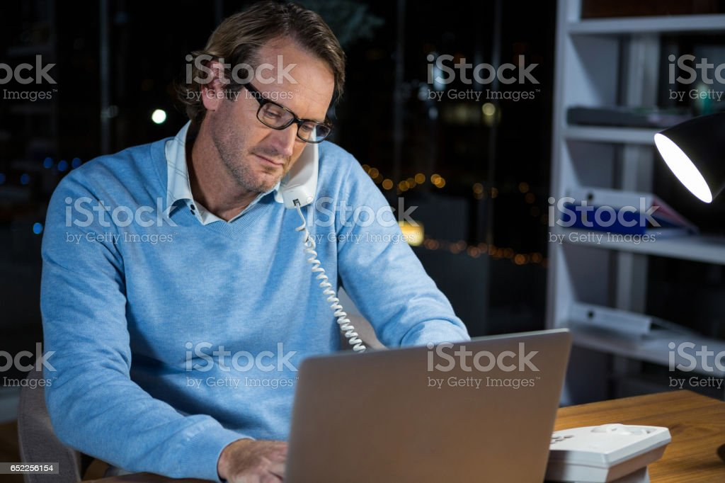 Businessman talking on phone while working in office stock photo