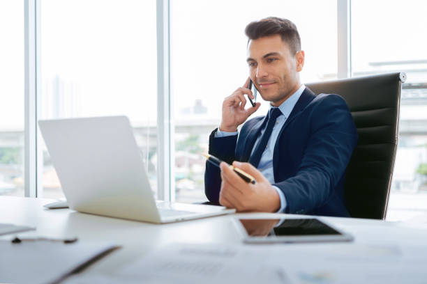 Businessman talking on smartphone and working on laptop computer stock photo