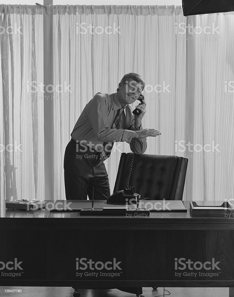 Businessman talking on telephone in office, smiling stock photo