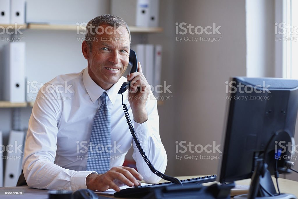 Businessman talking on the phone in front of a computer royalty-free stock photo
