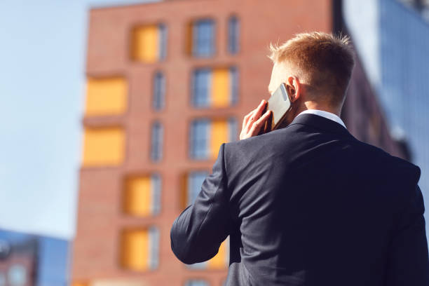 Businessman talking on the phone on the background of business building stock photo