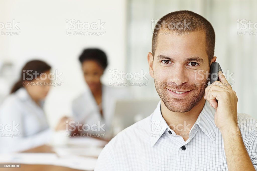 Businessman talking over cellphone with colleagues in the background royalty-free stock photo