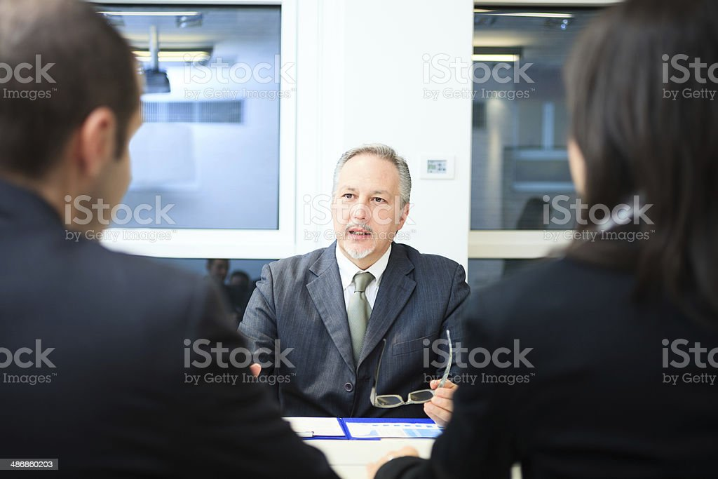 Businessman talking to a couple stock photo