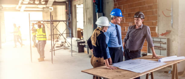 Businessman talking to architects at construction site stock photo