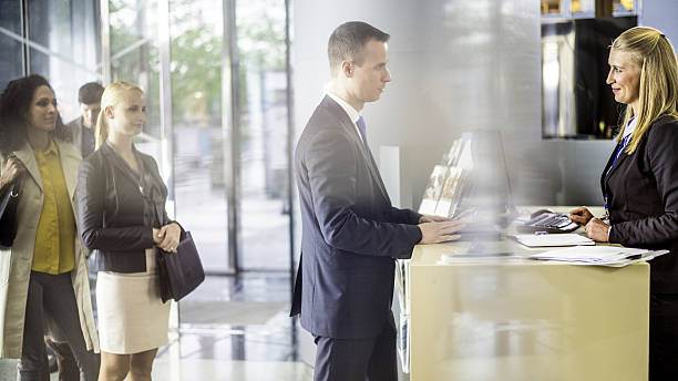 Businessman talking to bank teller at the counter – Foto