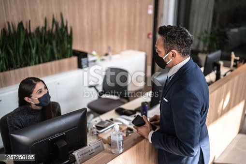 Businessman talking to receptionist on entrance of office's lobby - with face mask