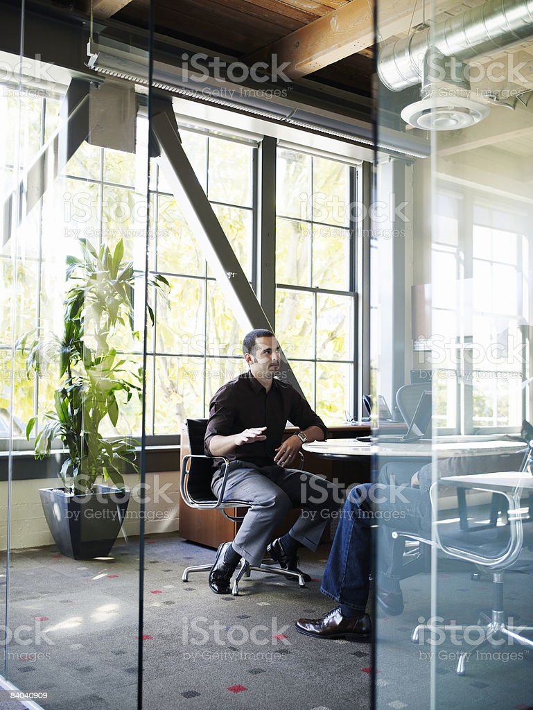Businessman talking with colleague in office royalty-free stock photo