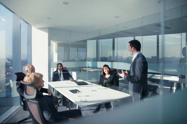 Businessman talking with colleagues in meeting stock photo