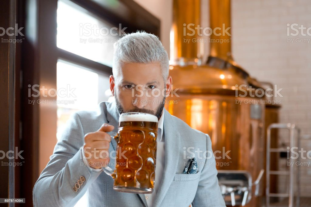 Businessman tasting freshly prepared beer at his micro brewery Portrait of male microbrewery owner drinking beer in his pub. Businessman tasting freshly prepared beer at his micro brewery. Adult Stock Photo