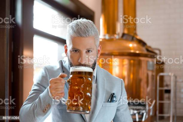 Businessman Tasting Freshly Prepared Beer At His Micro Brewery Stock Photo - Download Image Now