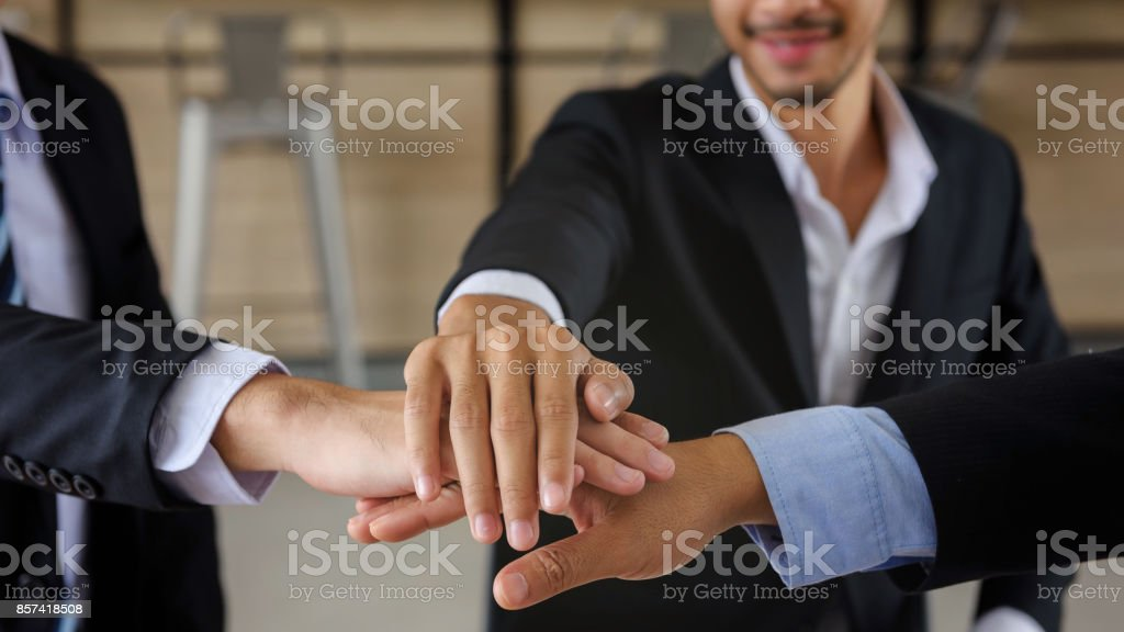businessman team joining and shaking hands together with smile face after getting agreement on project. symbol of teamwork ,companionship, unity for Business stock photo